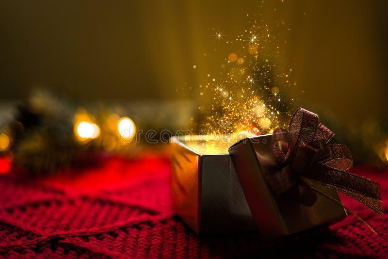 Regalo di Natale con le luci di magia delle particelle dell'oro immagine stock