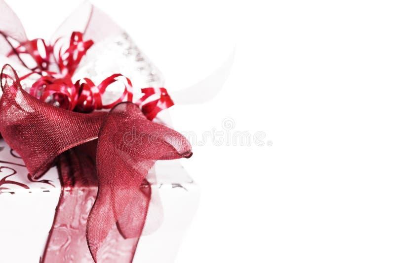Regalo di Natale d'argento con i nastri rossi immagini stock
