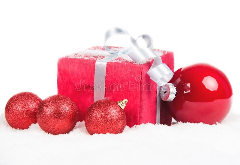 Regalo di Natale e palle su neve immagine stock