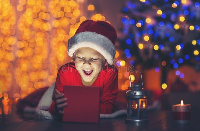 Regalo di Natale sorpreso di magia di apertura del bambino immagini stock