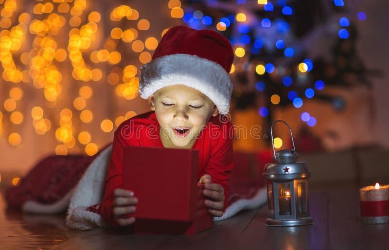 Regalo di Natale sorpreso di magia di apertura del bambino fotografia stock