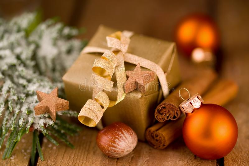 Regalo dorato sveglio di Natale con la decorazione su legno fotografia stock