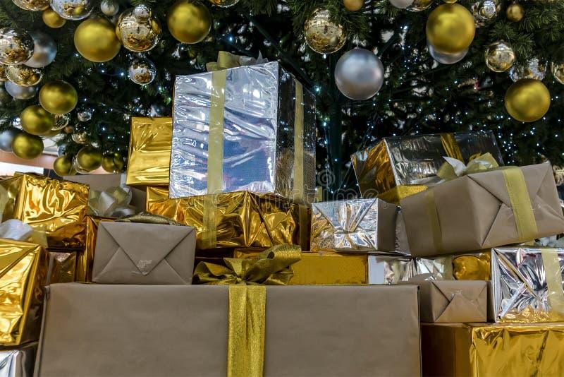Regalo en la mentira de empaquetado del oro brillante en el piso debajo del árbol Regalos de Papá Noel Muchos regalos de la Navid imagen de archivo libre de regalías