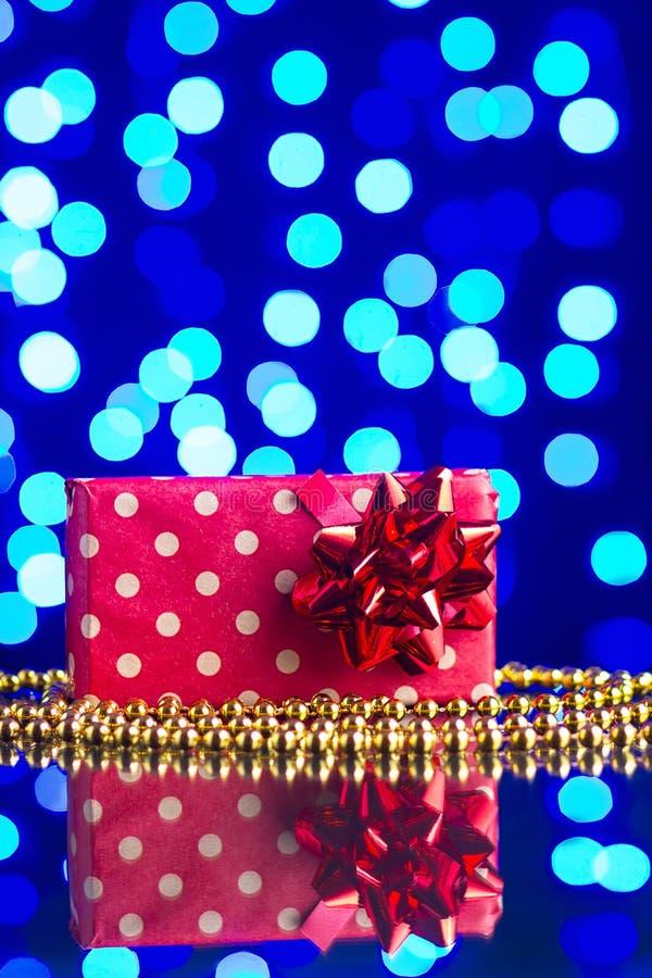 Regalo en paquete y gotas de oro en una tabla de cristal con un bokeh azul hermoso imágenes de archivo libres de regalías
