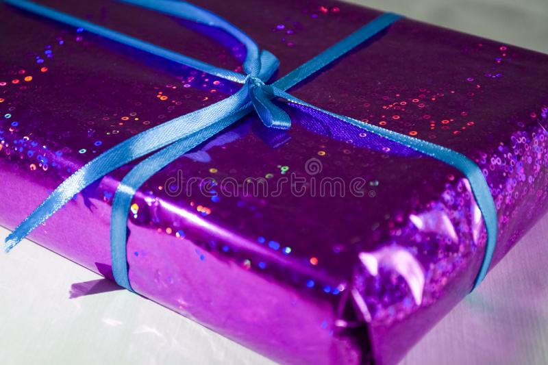 Regalo en una envoltura violeta y brillante con una cinta azul con un arco imagen de archivo