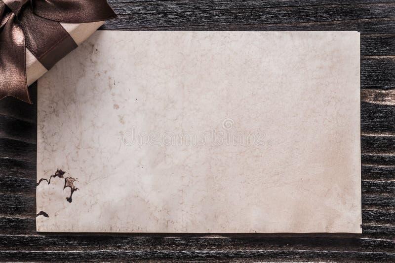 Regalo encajonado con el documento del arco sobre el tablero de madera del vintage fotos de archivo