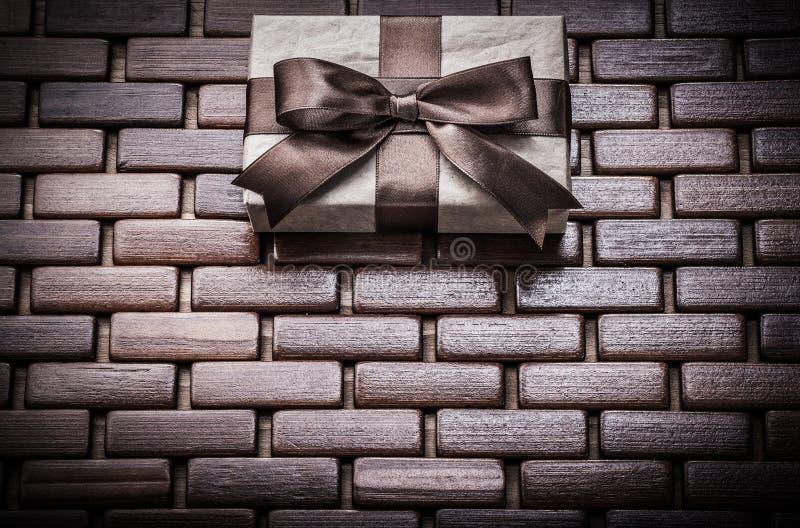 Regalo encajonado con la cinta en estera de mimbre de madera imágenes de archivo libres de regalías