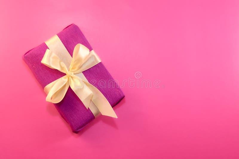 Regalo envuelto y adornado con un arco ligero en un fondo rosado con el espacio de la copia Endecha plana, visión superior Copie  fotos de archivo libres de regalías