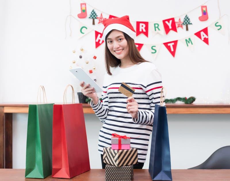 Regalo feliz de la Navidad de la compra de la tarjeta de crédito del uso de la mujer de Asia con el móvil imagenes de archivo