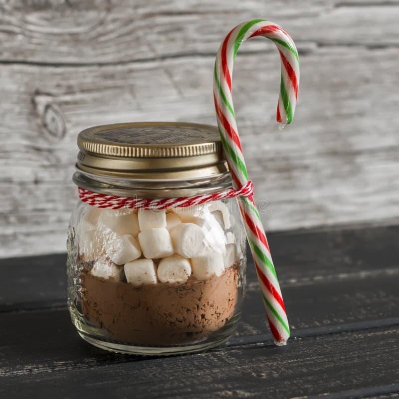 Regalo hecho en casa de la Navidad - ingredientes para hacer el chocolate caliente con las melcochas en un tarro de cristal imagenes de archivo