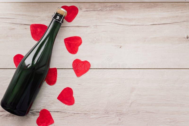 Regalo, il cuore e la bottiglia di vino rosso per un giorno romantico del ` s del biglietto di S. Valentino di festa immagine stock