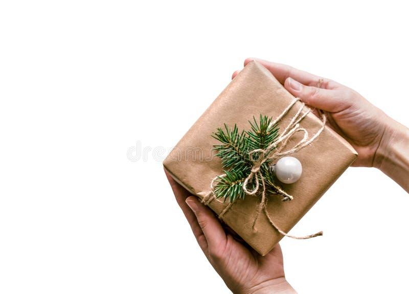 Regalo isolato in mani avvolte in carta kraft su fondo bianco, decorato in stile eco Fondo di Natale per immagini stock