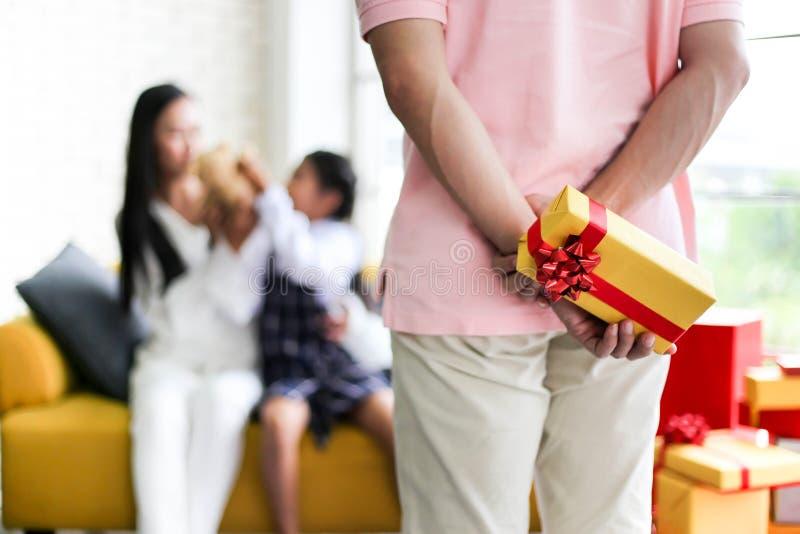 Regalo nascondentesi dell'uomo per il genitore ed il piccolo bambino divertendosi vicino a Chri fotografie stock