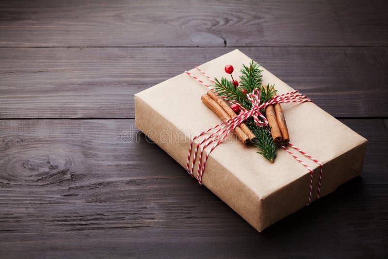 Regalo o actual caja envuelta en el papel de Kraft con la decoración de la Navidad en la tabla de madera del vintage Copie el esp foto de archivo