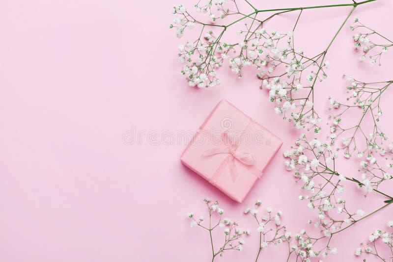 Regalo o actuales caja y flor en la tabla rosada desde arriba Color en colores pastel Tarjeta de felicitación estilo plano de la  foto de archivo libre de regalías