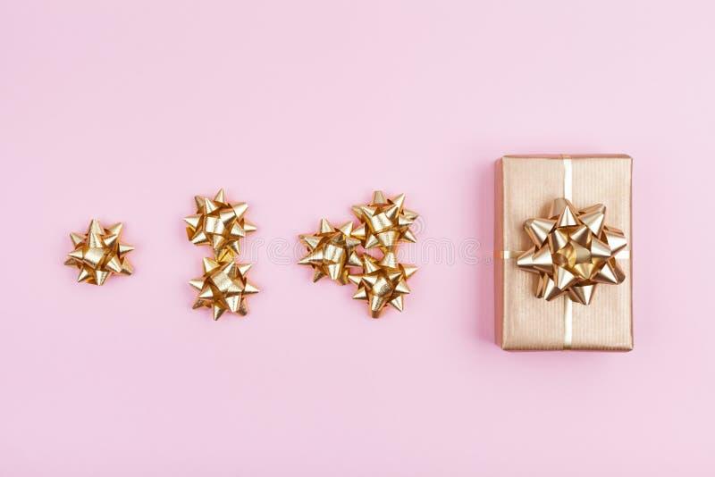 Regalo o scatola attuale che si avvolge in carta dorata con gli archi sulla vista superiore del fondo pastello rosa Composizione  immagini stock libere da diritti