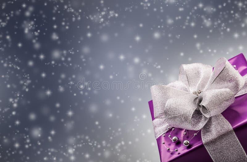 Regalo púrpura de la Navidad o de la tarjeta del día de San Valentín con el fondo de plata del gris del extracto de la cinta imagen de archivo