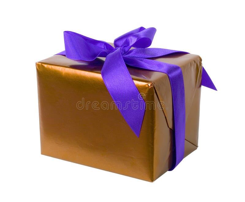 Regalo - papel de oro y cinta púrpura fotos de archivo