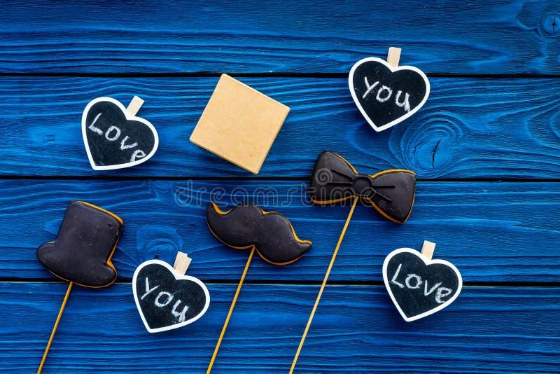 Regalo para el hombre en cumpleaños La caja de regalo entre las galletas en la forma del bigote, el sombrero, la corbata de lazo  fotos de archivo