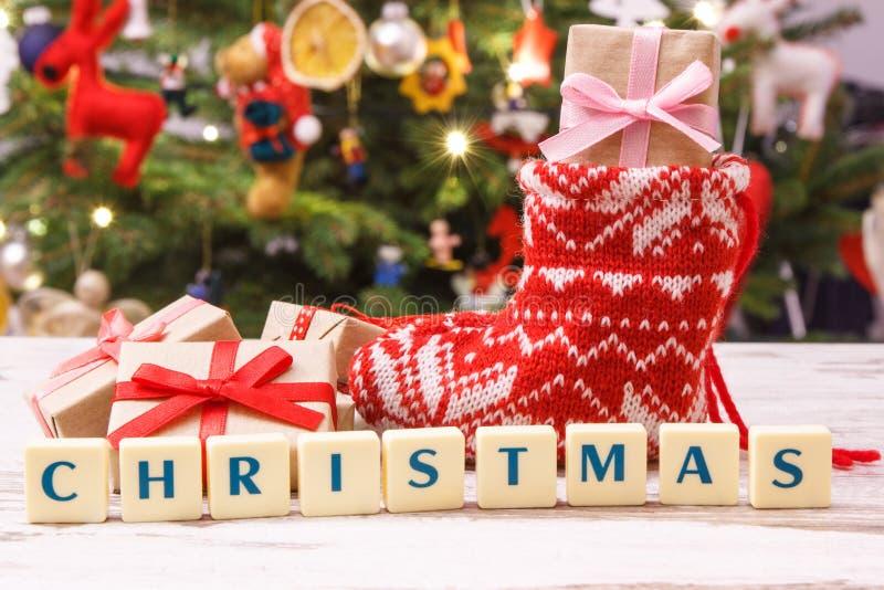 Regalo per il Natale con il calzino di lana rosso, albero di Natale con la decorazione, concetto festivo di tempo immagine stock