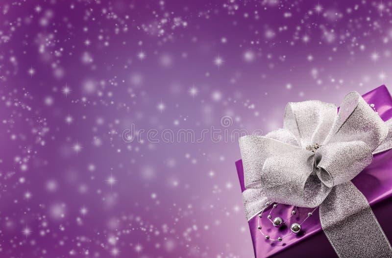 Regalo porpora del biglietto di S. Valentino o di Natale con il fondo d'argento di porpora dell'estratto del nastro immagini stock