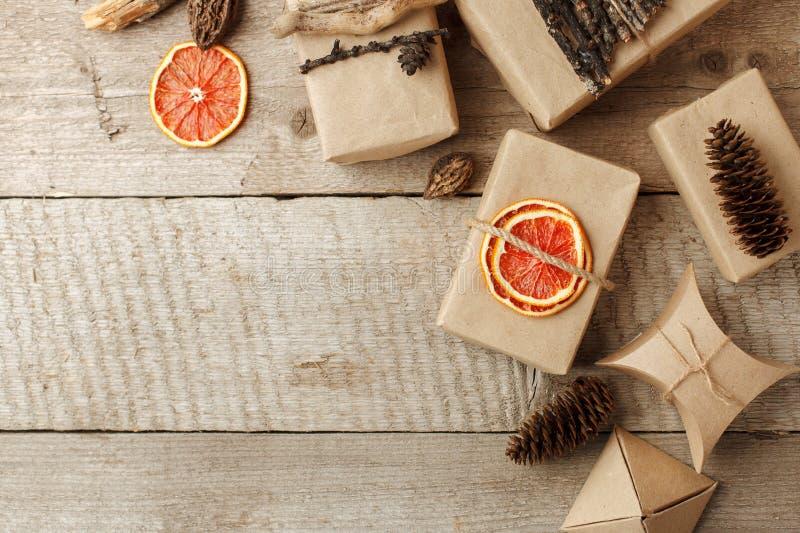 Regalo rústico envuelto en papel del arte con la decoración natural en la tabla de madera con los conos del pino El eco simple pr imagen de archivo