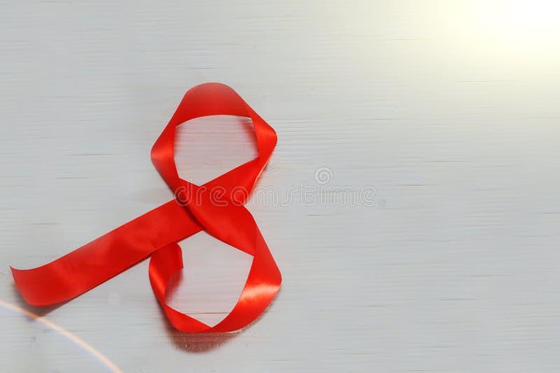 Regalo rojo de la celebración de la cinta bajo la forma de 8 dígitos en una luz Día feliz del ` s de las mujeres, los ocho de mar imagenes de archivo