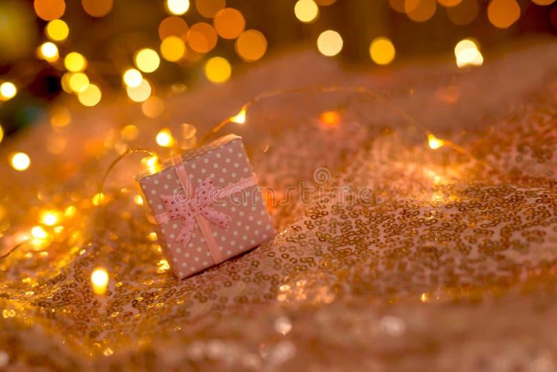 Regalo rosa su un fondo di corallo con le luci vaghe di una ghirlanda fotografia stock libera da diritti