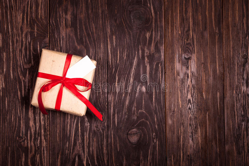 Regalo rustico con un nastro rosso su fondo di legno immagine stock libera da diritti