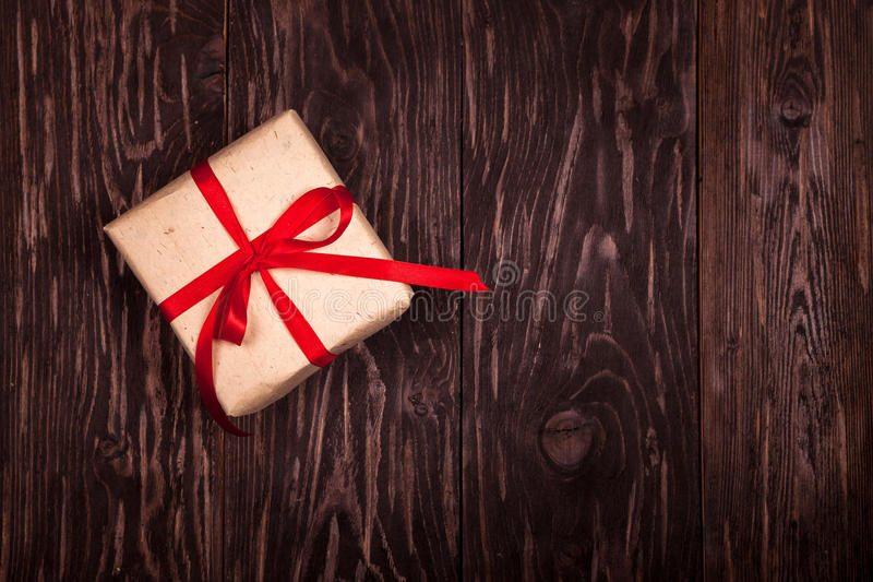 Regalo rustico con un nastro rosso su fondo di legno fotografia stock libera da diritti