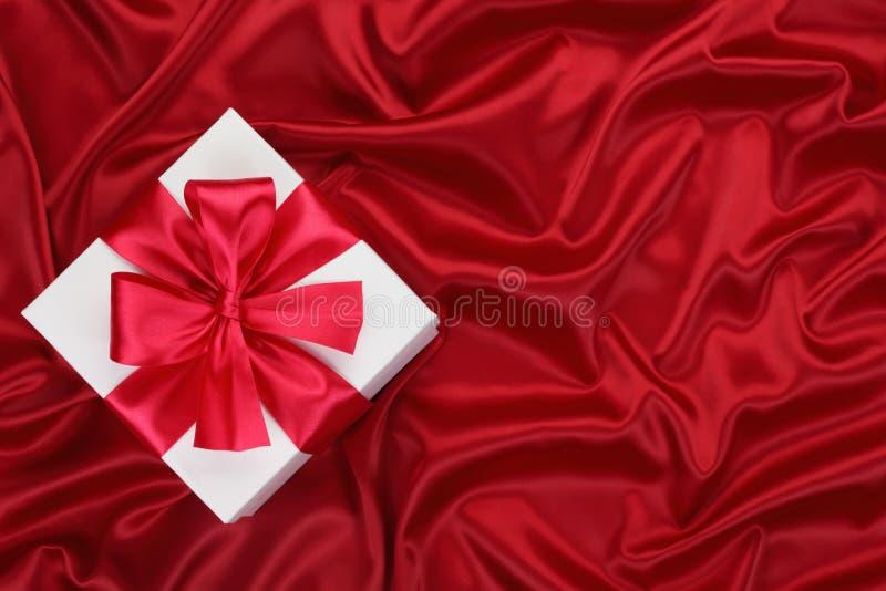 Regalo sulla seta rossa. fotografia stock libera da diritti