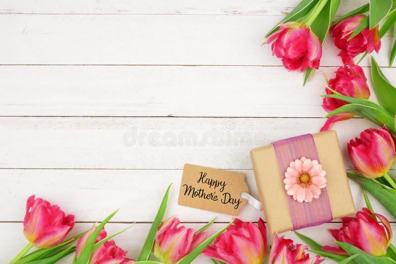 Regalo y etiqueta felices del día de madres con la frontera de la esquina de flores rosadas contra un fondo de madera blanco fotos de archivo libres de regalías