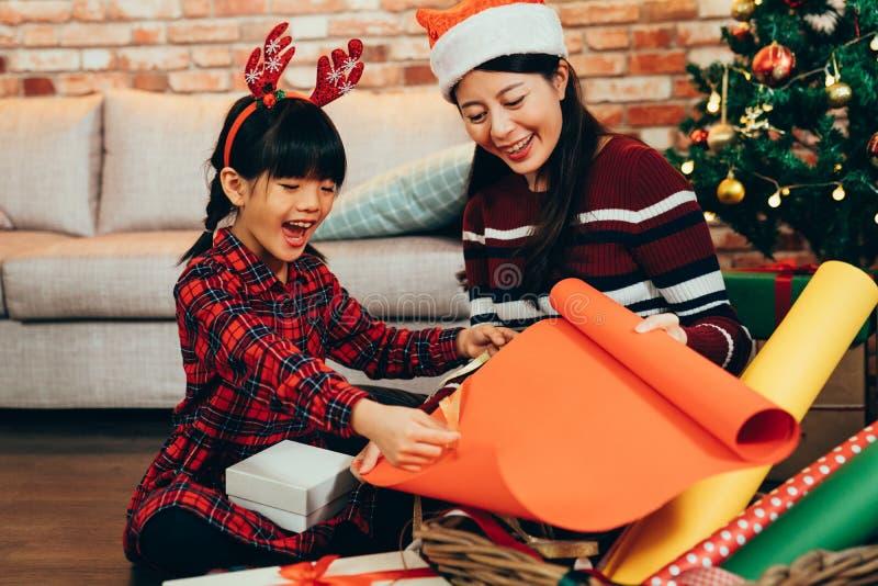 Regalos de empaquetado sonrientes de la Navidad de la mujer y del niño imagenes de archivo