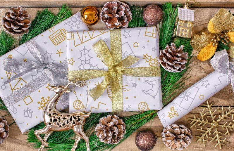 Regalos de la Navidad, cajas de los regalos, abeto, con los conos y los ciervos en un fondo de madera imagenes de archivo