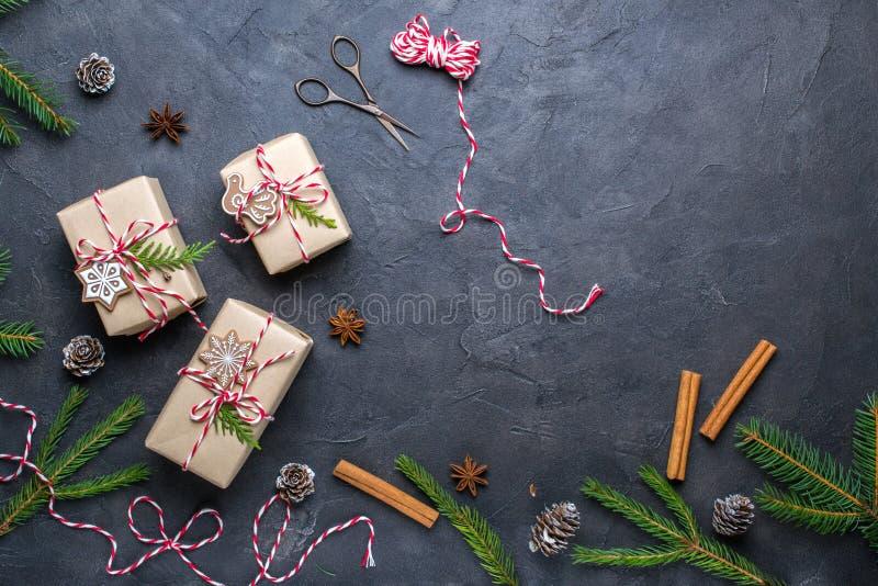Regalos de la Navidad del embalaje Cajas de regalo de la Navidad y decoraciones, ramas del pino en la tabla oscura Presente adorn fotografía de archivo