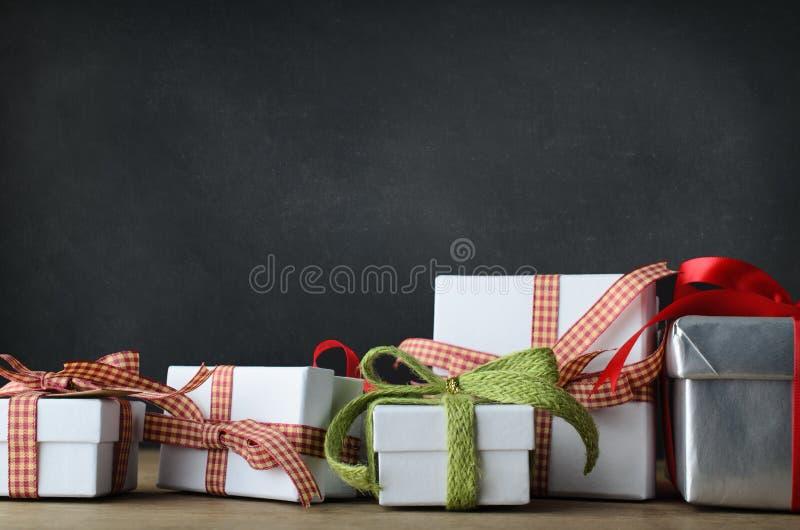 Regalos de la Navidad en el escritorio con el fondo de la pizarra imagenes de archivo