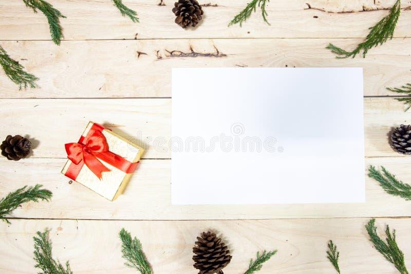 Regalos de la Navidad en un fondo de madera blanco con los conos del árbol y del pino de abeto encendido, regalos del Año Nuevo,  foto de archivo