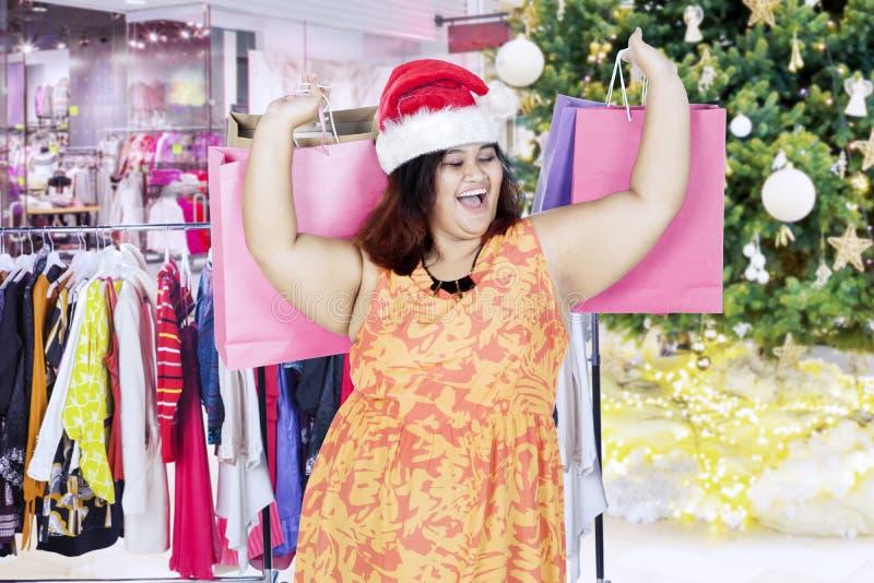 Regalos de la Navidad de la mujer que llevan gorda en la alameda foto de archivo