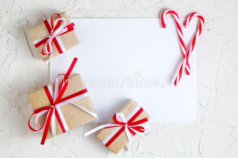 Regalos de la Navidad y bastón de caramelo con con la tarjeta de felicitación en blanco imagen de archivo