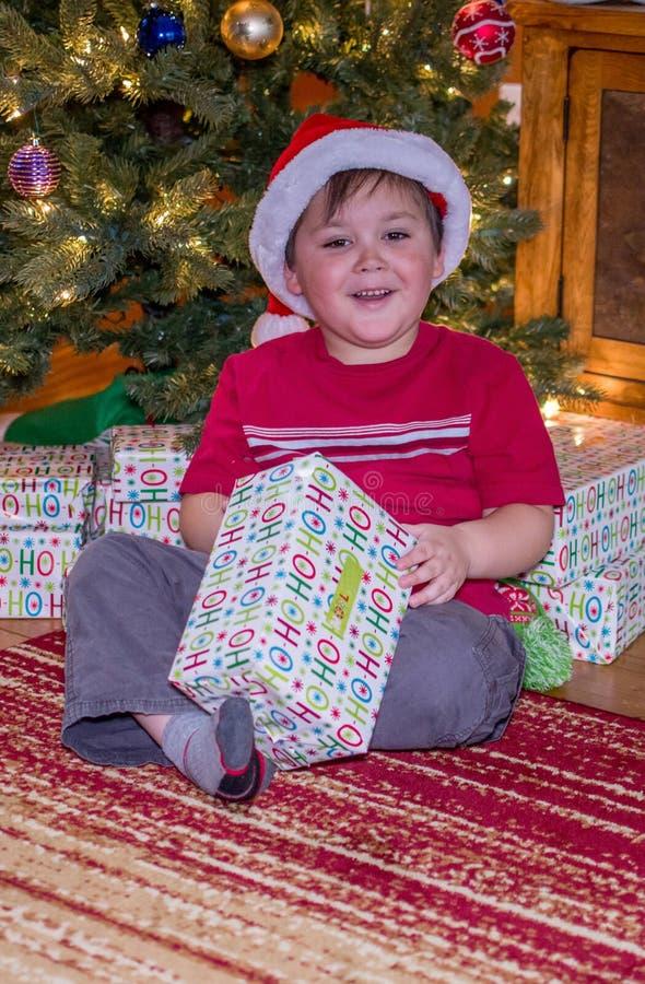 Regalos de Navidad de apertura del muchacho en el tiempo de la Navidad imagenes de archivo