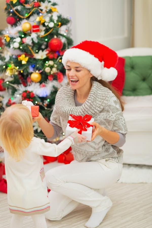 Regalos de Navidad cambiantes de la mama y del bebé foto de archivo libre de regalías