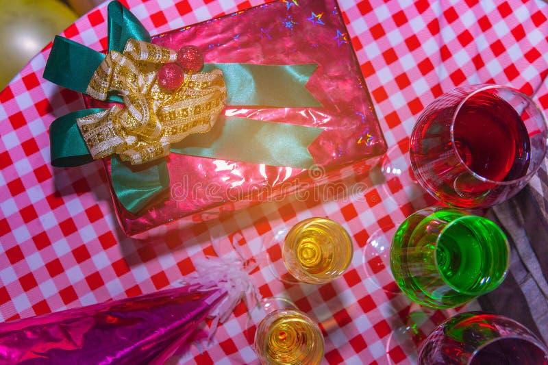Regalos de Navidad con la cinta roja puesta en una tabla de madera con las copas de vino y la comida imagen de archivo libre de regalías