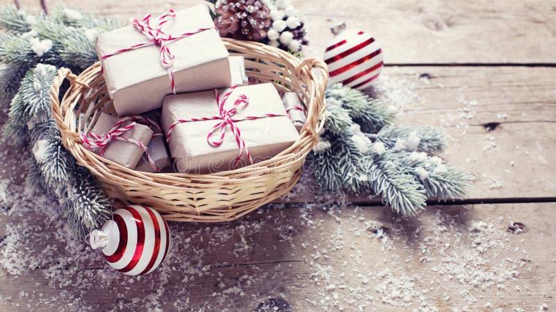 Regalos de Navidad en cesta, árbol de la piel y bolas decorativas en a imagenes de archivo