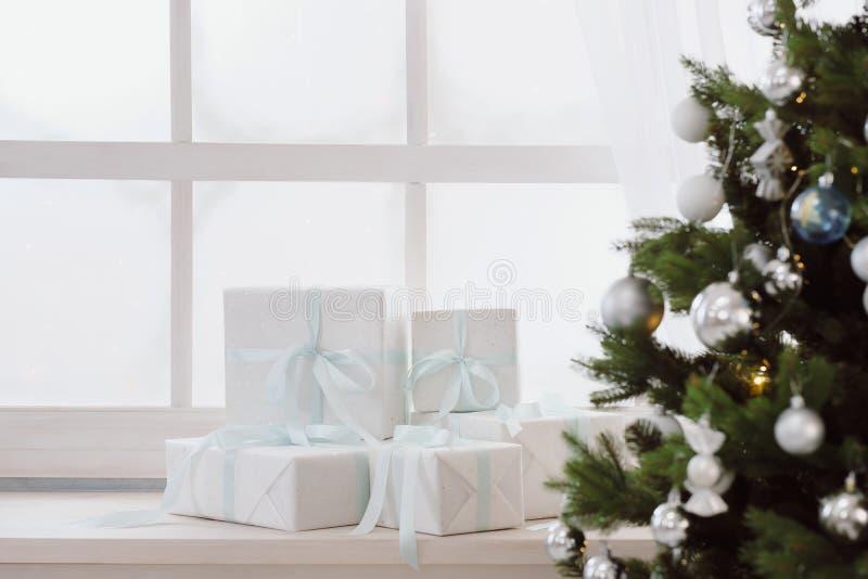 Regalos de Navidad en las cajas blancas en una ventana debajo de un árbol de navidad foto de archivo libre de regalías