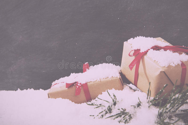 Regalos de Navidad en nieve contra un vintage Fi retro de la pizarra fotografía de archivo