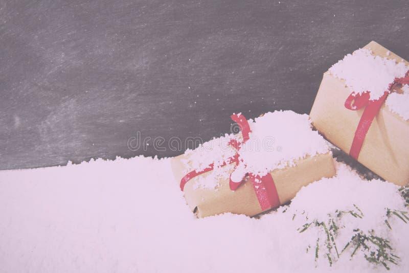 Regalos de Navidad en nieve contra un vintage Fi retro de la pizarra foto de archivo