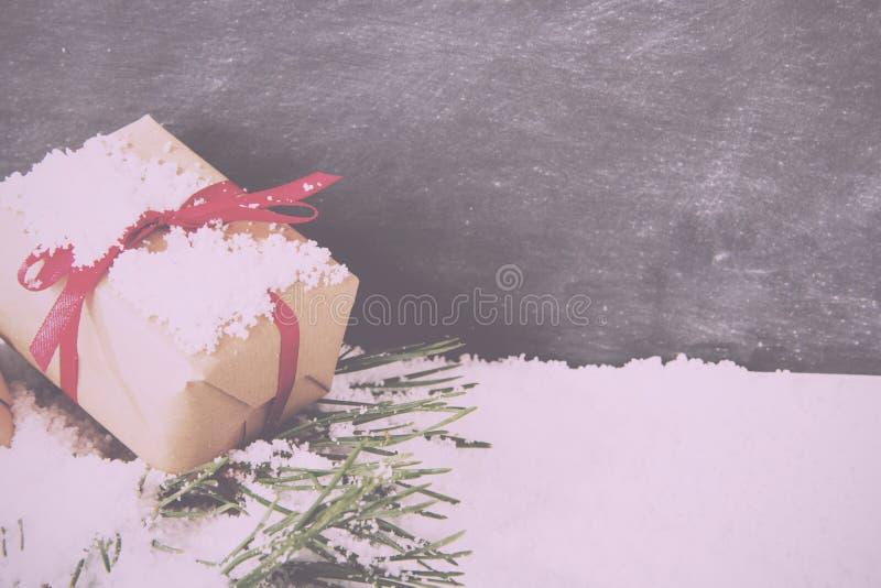 Regalos de Navidad en nieve contra un vintage Fi retro de la pizarra imagenes de archivo