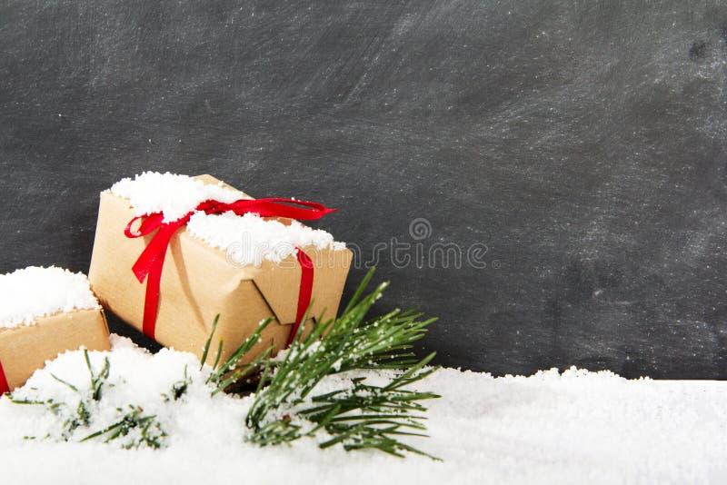 Regalos de Navidad en nieve contra una pizarra fotos de archivo libres de regalías