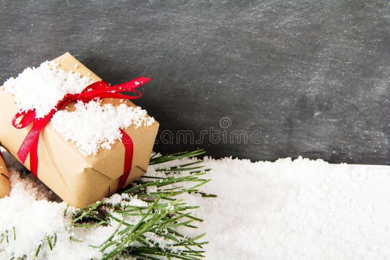 Regalos de Navidad en nieve contra una pizarra imagen de archivo libre de regalías