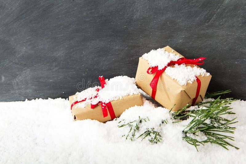 Regalos de Navidad en nieve contra una pizarra foto de archivo